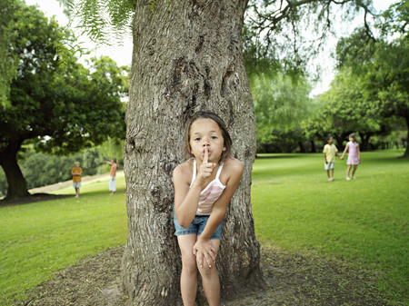 Girl (7-9) with finger on lips playing hide and seek in park, hiding from friends behind tree Stock Photo