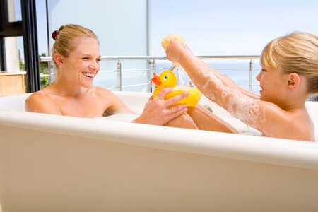 wetting: Mother and daughter (6-8) in bath outdoors, woman with rubber duck, smiling at each other LANG_EVOIMAGES