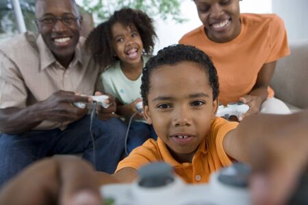 differential focus: Family playing video games console on sofa at home, smiling, front view (differential focus)