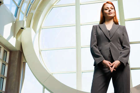 ginger hair: Confident businesswoman, with ginger hair, wearing grey suit, standing beside window, portrait, low angle view