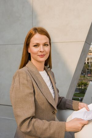 ginger hair: Businesswoman, with ginger hair, standing on balcony, holding document, smiling, side view, portrait
