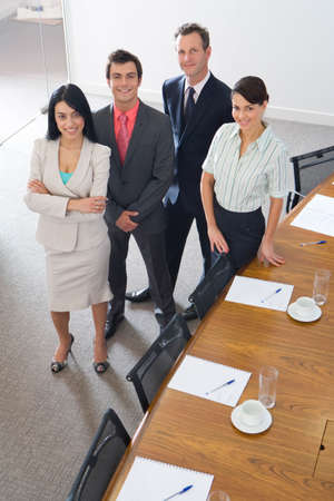conference room table: Businessmen and women by conference room table, smiling, portrait, elevated view
