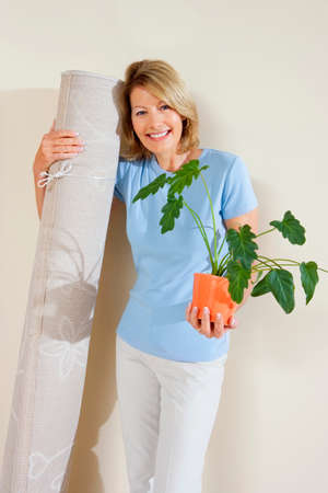 fortysomething: Senior woman holding pot plant and rolled up carpet, moving house, smiling, front view, portrait LANG_EVOIMAGES