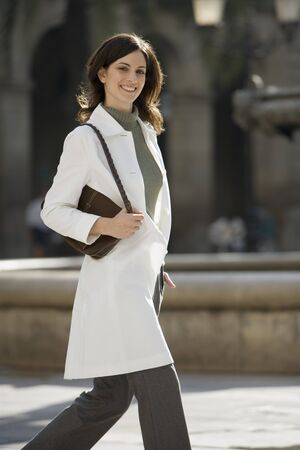 only mid adult women: Woman in polo neck jumper and white coat walking in plaza, carrying handbag, smiling, portrait