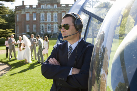 helicopter pilot: Helicopter pilot in sunglasses by helicopter, wedding party in background LANG_EVOIMAGES