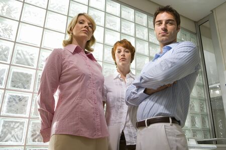 glass block: Businessman and women standing by glass block wall, portrait, low angle view LANG_EVOIMAGES