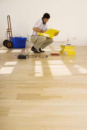 moving images: Businessman crouching in empty office, using telephone plugged into floor socket, opening folder