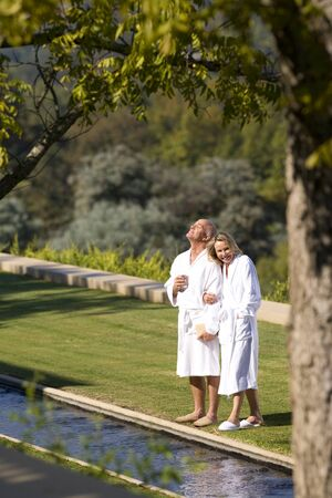 bath robes: Mature couple wearing white bath robes, standing on lawn together, elevated view