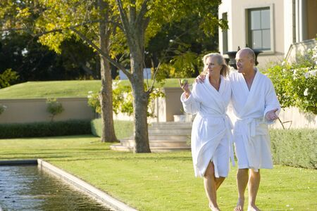 bath robes: Mature couple wearing white bath robes walking by swimming pool, smiling