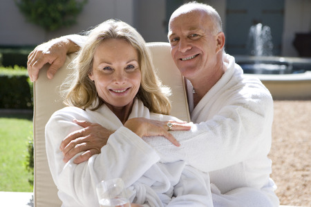 bath robes: Mature couple wearing white bath robes, sitting outdoors, smiling, portrait, close-up LANG_EVOIMAGES