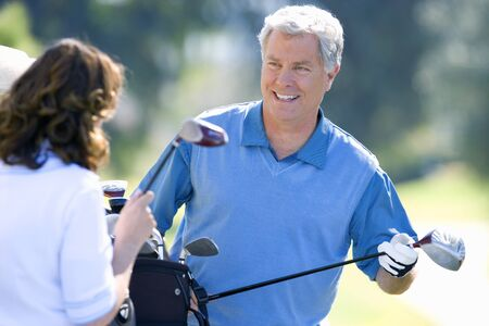 golf bag: Mature couple playing golf, man in blue tank top taking driver from golf bag, smiling (differential focus)