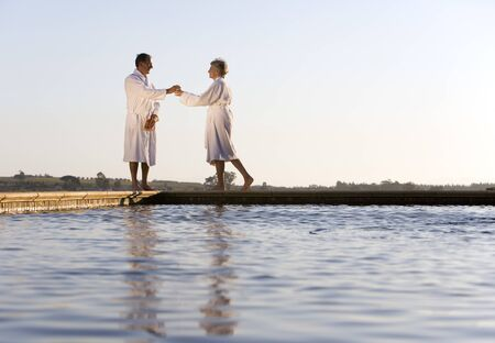 bath robes: Senior couple wearing white bath robes, standing outdoors by swimming pool, side view