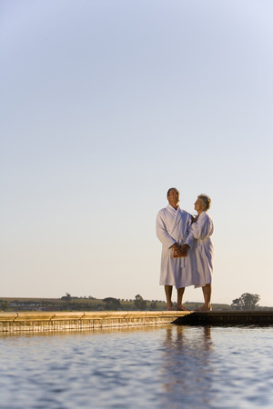bath robes: Senior couple wearing white bath robes, embracing outdoors by swimming pool, smiling, eyes closed LANG_EVOIMAGES