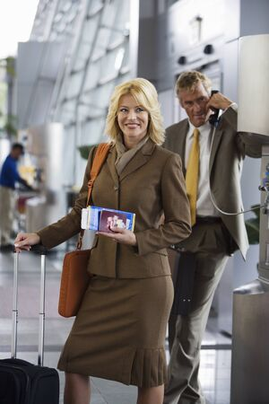 pay phone: Businessman using pay phone in airport terminal, focus on businesswoman with luggage and ticket, portrait LANG_EVOIMAGES
