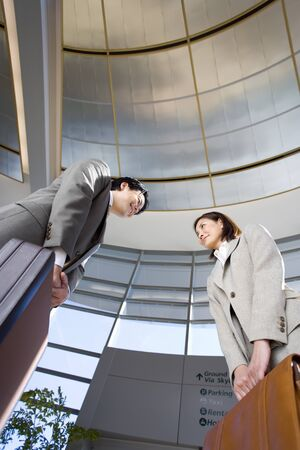 tilt view: Businessman and woman meeting in airport, carrying briefcases, smiling, side view, low angle view (tilt) LANG_EVOIMAGES