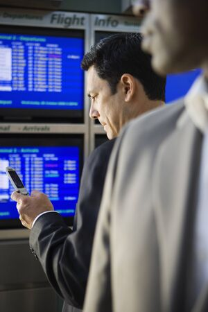 differential focus: Two businessmen waiting in airport departure lounge, man reading text message on mobile phone  (differential focus)