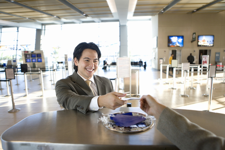 two person only: Businessman checking in at airport, receiving boarding pass from check-in attendant, view from behind check-in desk LANG_EVOIMAGES