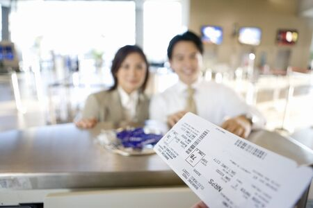checking in: Business couple checking in at airport, focus on boarding passes in check-in attendant's hands in foreground, view from behind check-in desk