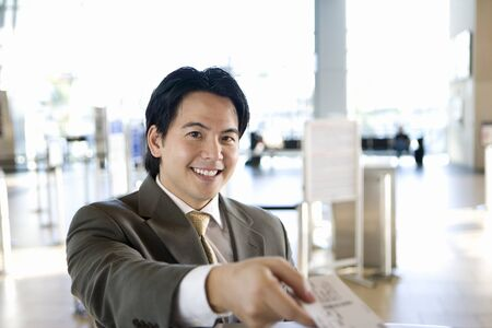 differential: Businessman checking in at airport, receiving boarding pass from check-in attendant, smiling, portrait, view from behind check-in desk (differential focus)