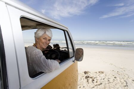 beach window: Senior woman looking out of window of camper van on beach, smiling, portrait