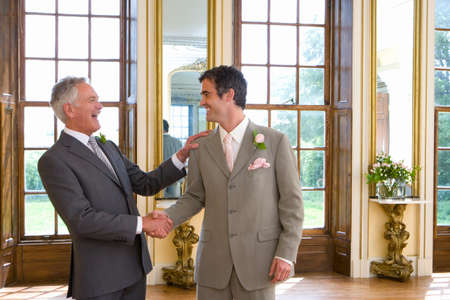 other side of: Groom and usher shaking hands, smiling at each other, side view