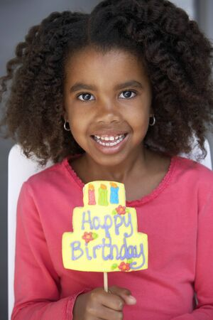 front view: Girl (7-9) holding birthday card, smiling, front view, close-up, portrait