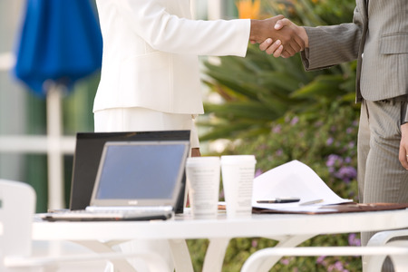 midsection: Two businesswomen shaking hands beside pavement cafe table, side view, mid-section