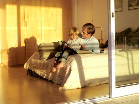 sliding doors: Father and son (5-7) sitting on bed, looking at photo album, view through open sliding doors LANG_EVOIMAGES