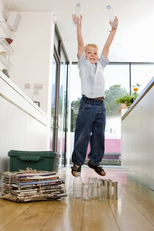 separating: Boy (2-4) by recycling in kitchen, jumping, holding bottles overhead