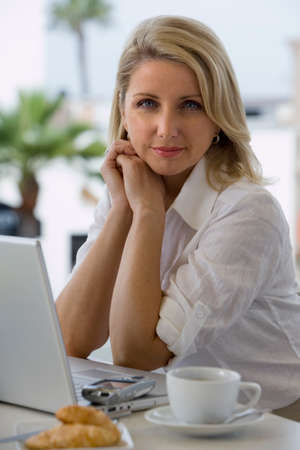 one mid adult woman only: Businesswoman sitting at balcony table with laptop, smiling, side view, portrait LANG_EVOIMAGES
