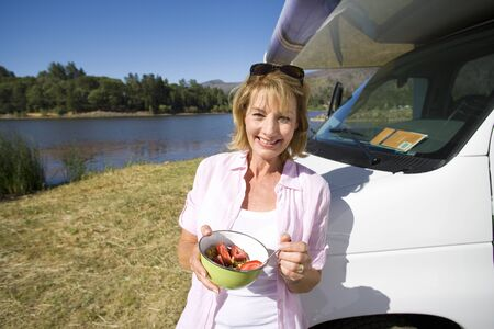 motor home: Mature woman with breakfast bowl by motor home and lake, smiling, portrait LANG_EVOIMAGES
