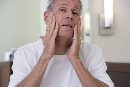 man front view: Senior man, in white t-shirt, applying moisturiser to face in bathroom, close-up, front view, portrait