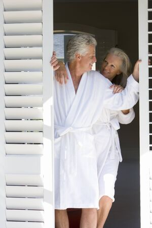 bath robes: Mature couple wearing white bath robes, standing in doorway, smiling at each other