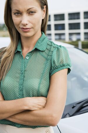 only mid adult women: Woman in green short-sleeved blouse standing beside car, arms folded, close-up, portrait