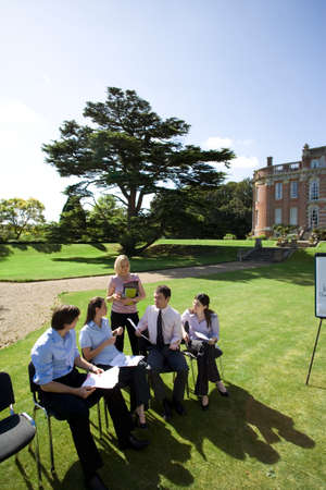 out of context: Businessmen and women on chairs on grass by manor house, in training course, elevated view