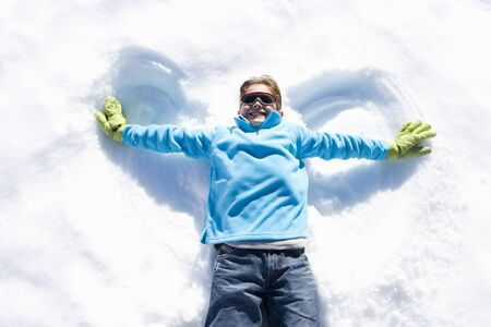 indentation: Boy (7-9) lying in snow making angel wings, smiling, overhead view LANG_EVOIMAGES