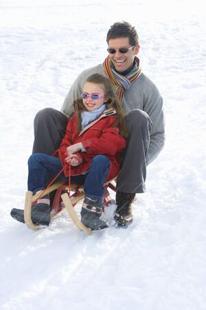 to steer a sledge: Father and daughter (7-9) riding sled down snow slope, smiling, low angle view LANG_EVOIMAGES