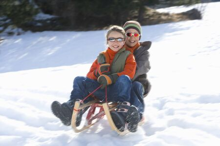 to steer a sledge: Boy and girl (7-9) riding sled down snow slope, wearing sunlgasses, smiling, low angle view LANG_EVOIMAGES