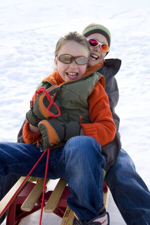 to steer a sledge: Boy and girl (7-9) on sled in snow, wearing sunglasses, smiling, portrait LANG_EVOIMAGES