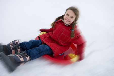 blurred motion: Girl (7-9) riding down snow on sled, smiling, portrait, elevated view (blurred motion) LANG_EVOIMAGES