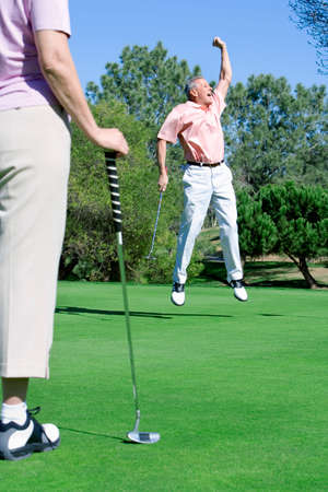 putt: Mature couple playing golf, man punching air in delight at successful putt, woman watching in foreground