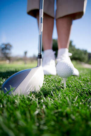 tee off: Mature woman preparing to tee off with driver on golf course, close-up, low section (surface level)