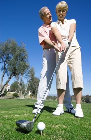 tee off: Mature couple playing golf, man standing behind woman preparing to tee off, offering advice and guidance, smiling (surface level)