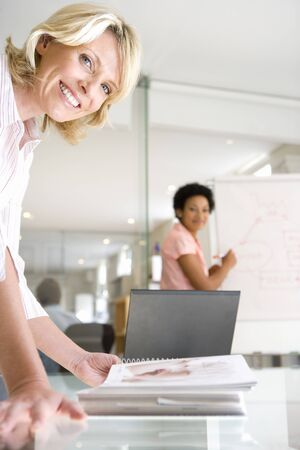 one on one meeting: Two businesswomen in meeting room, one looking at book on table, one using flipchart, smiling, portrait (differential focus) LANG_EVOIMAGES