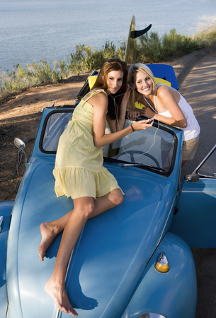 mp3 player: Teenage girls (17-19) listening to MP3 player on car bonnet, sharing headphones, elevated view