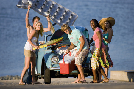 ice chest: Teenagers (17-19) standing beside car near water, carrying cool box and inflatable, smiling