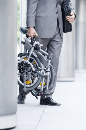 low section view: Businessman leaving office building, carrying folding commuter bicycle, side view, low section