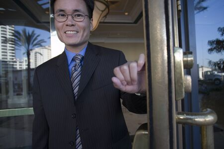exiting: Businessman in spectacles opening door, exiting building lobby, smiling, front view, portrait