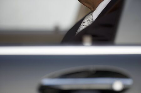 differential focus: Businessman sitting in car, view through window, side view, close-up (differential focus)