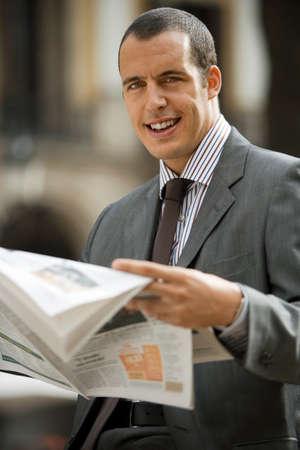 differential focus: Businessman reading newspaper, smiling, close-up, portrait, outdoors (differential focus)